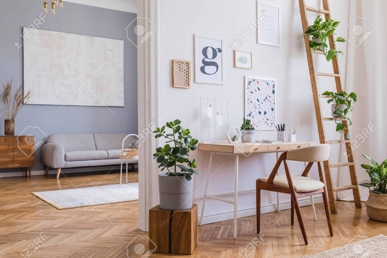 Modern and design home interior of open space with wooden desk, sofa, chair, a lot of plants, commode, mock up poster frames and elegant accessories. Stylish and minimalistic home decor. Template. - 134017492