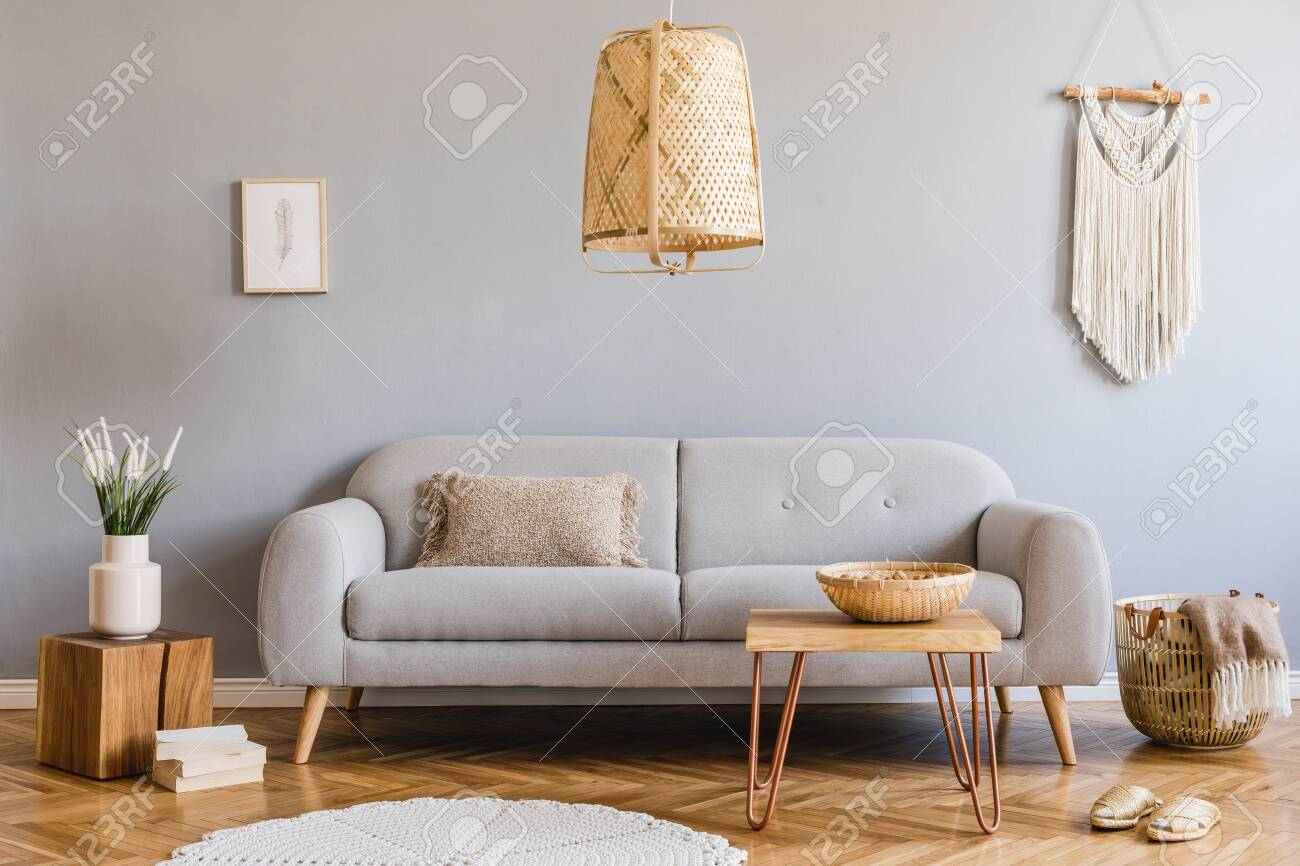 Minimalistic and design home interior of living room with gray sofa, wooden cube,, coffee table, pillow, beige macrame, mock up poster frame and elegant accessories. Stylish home decor. Template. - 135148106