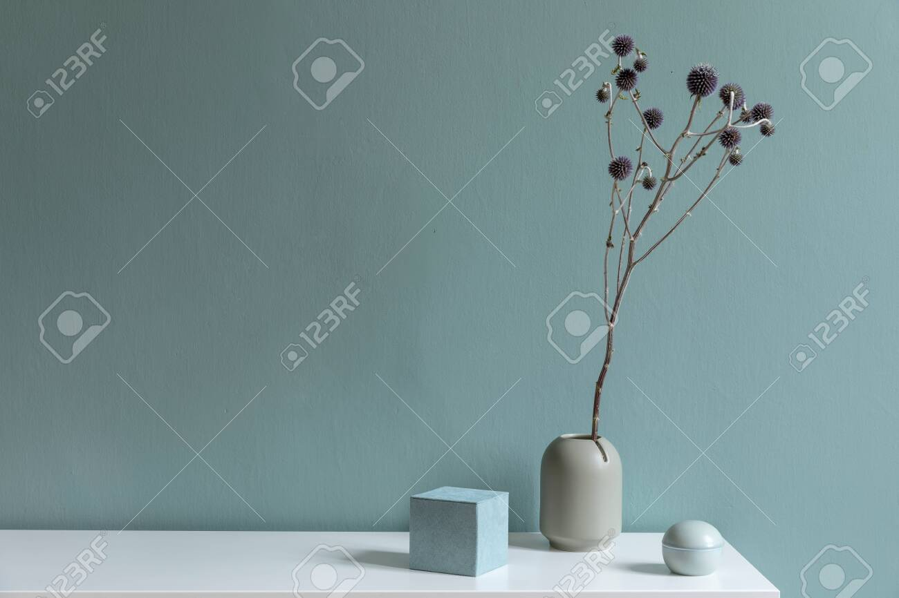 Minimalistic interior design of living room at nice apartment with stylish shelf, vase with flowers and elegant accessories. Copy space. Eucalyptus color concept. Template. - 137184581