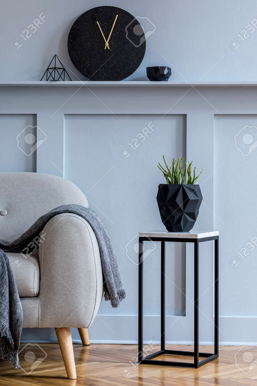 Stylish scandinavian interior of living room with gray sofa, plaid, black clock, wood paneling with shelf, marble stool, plants and elegant personal accessories in design home decor. - 157530440