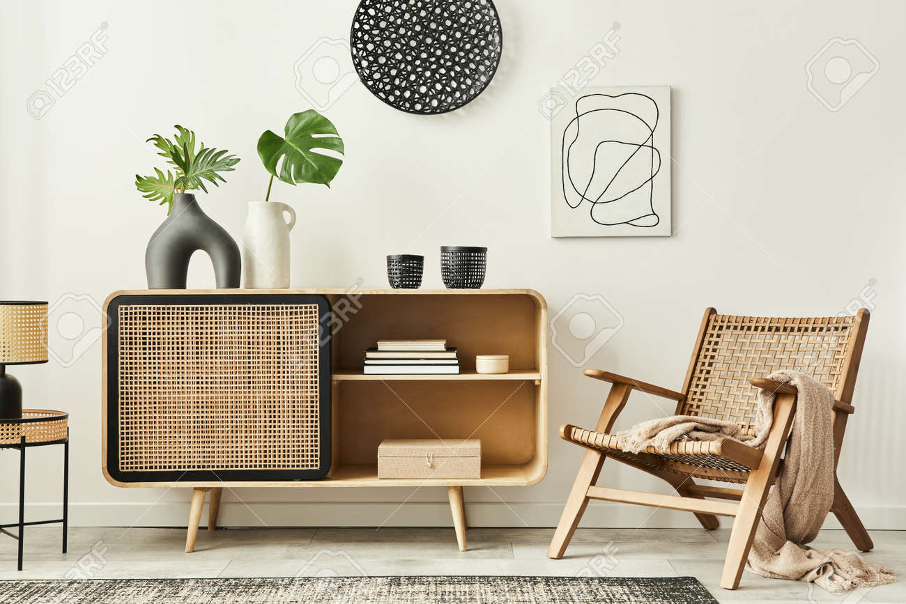 Stylish scandinavian living room interior of modern apartment with wooden commode, design armchair, carpet, leaf in vase, table lamp and personal accessories in unique home decor. Template. - 166415560