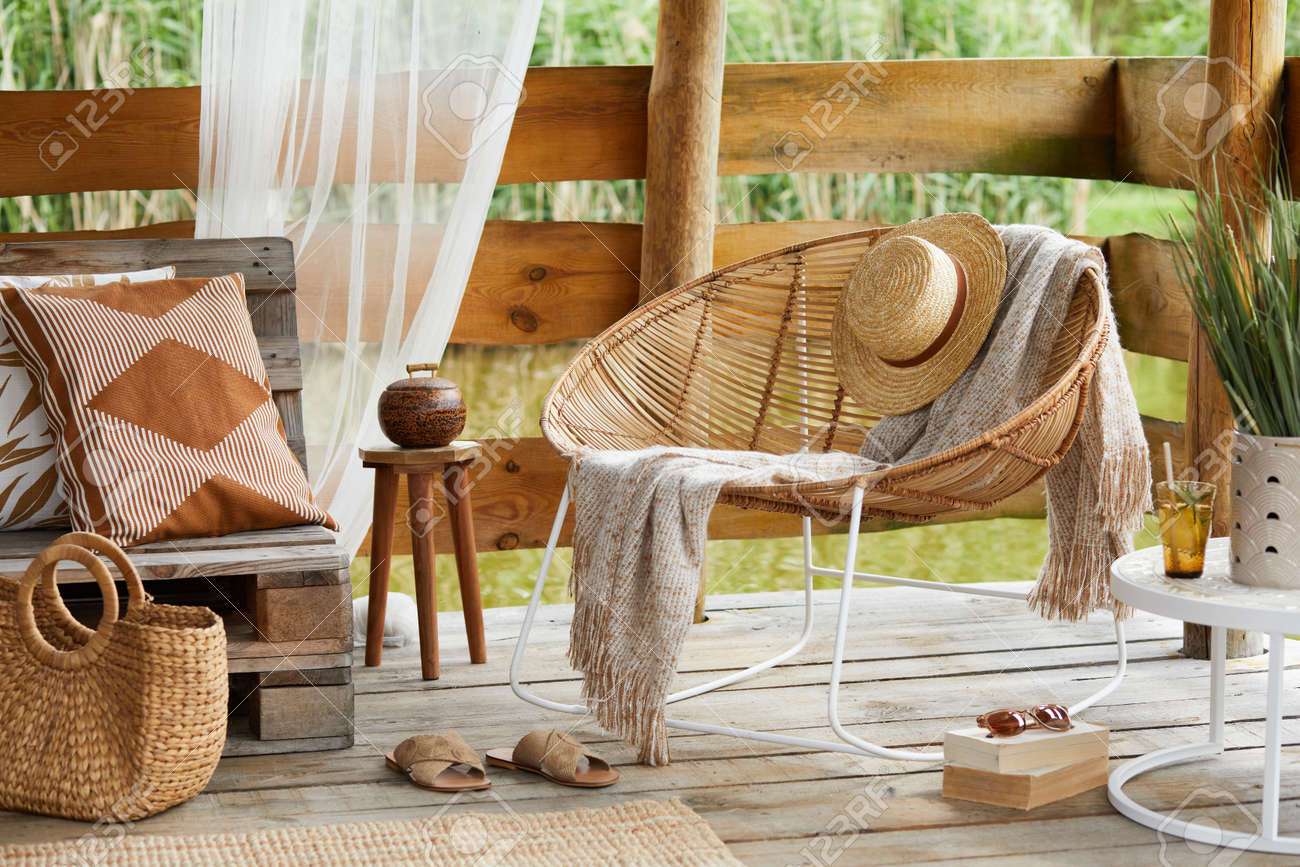 Interior design of summer gazebo by the lake with stylish rattan armchair, coffee table, sofa, pillows, plaid and elegant accessories in modern decor. Summer vibes. - 168356123