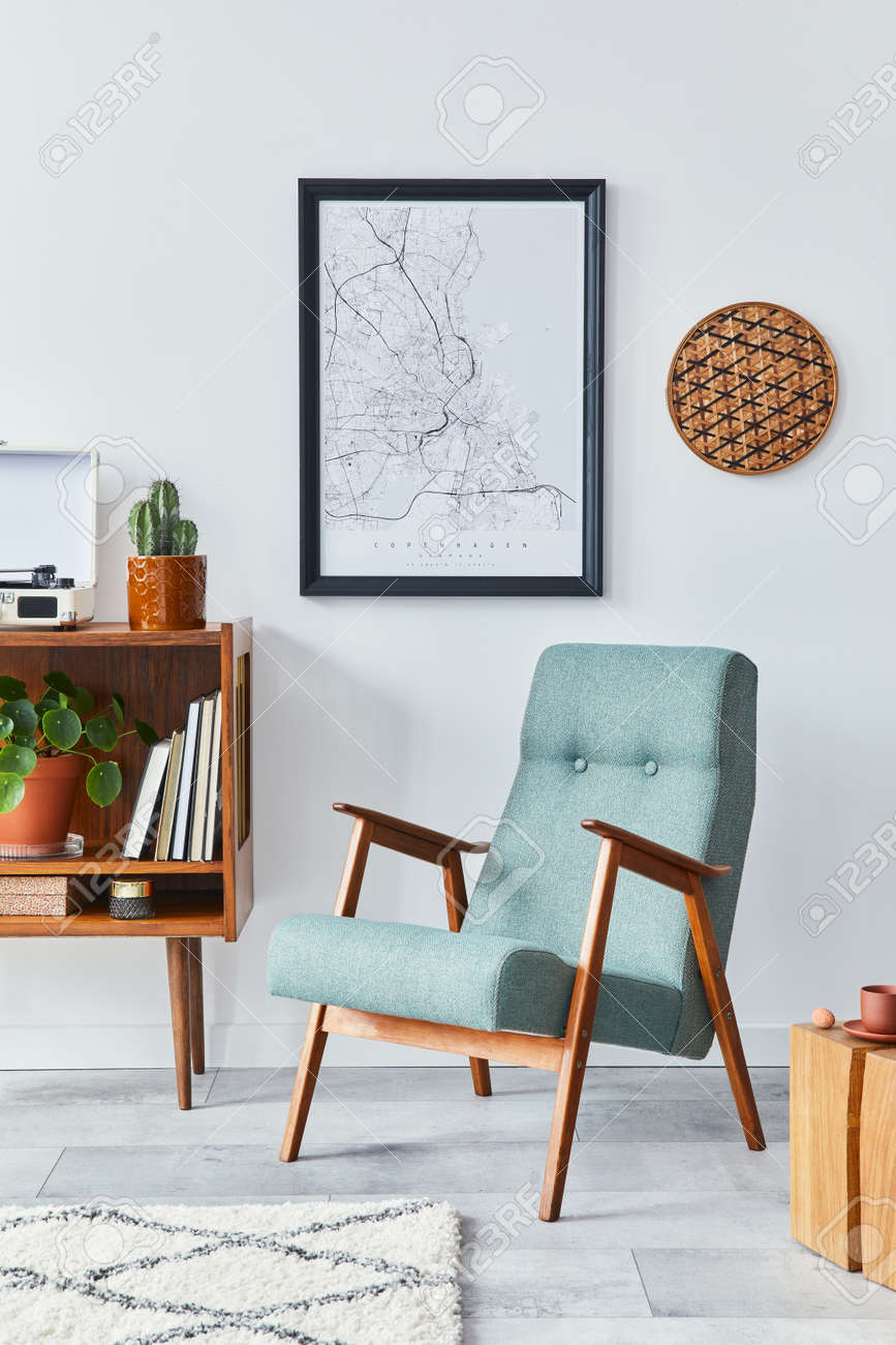 Retro composition of living room interior with mock up poster map, wooden shelf, book, stool, armchair, plant, cacti, vinyl recorder and personal accessories in stylish home decor. - 168356127