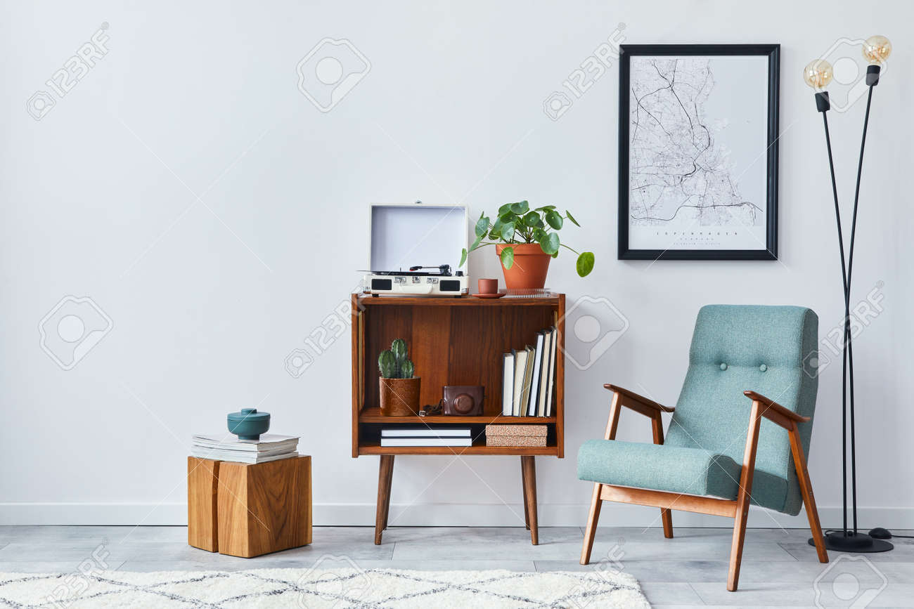 Modern retro composition of living room interior with design wooden cabinet, stylish armchair, mock up poster map, plants, vinyl recorder, books and personal accessories in home decor. Template. - 168356132