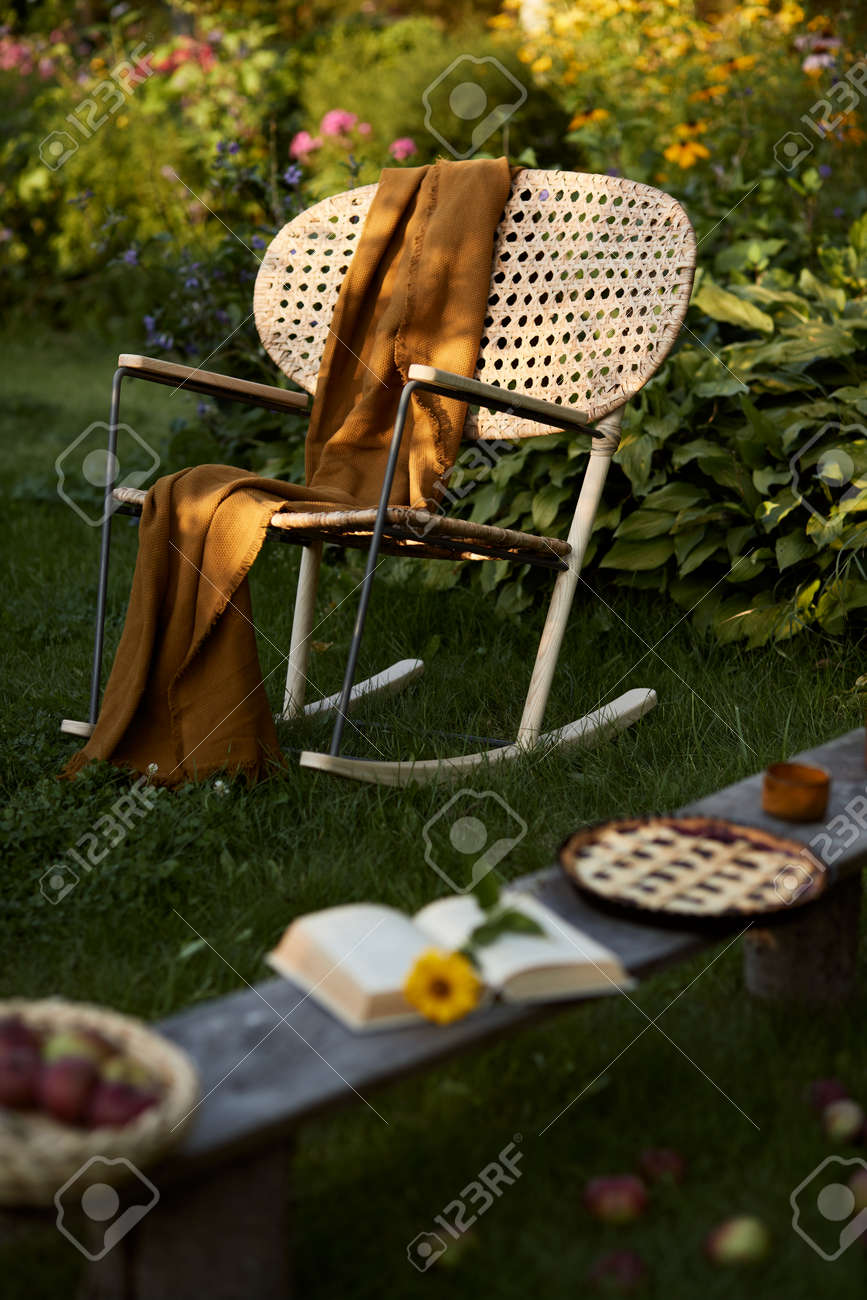 Stylish composition of countryside garden with design rattan armchair, wooden bench, plaid, food, drinks and elegant accessories. A lot of colorful flowers. Summer mood. - 168356136