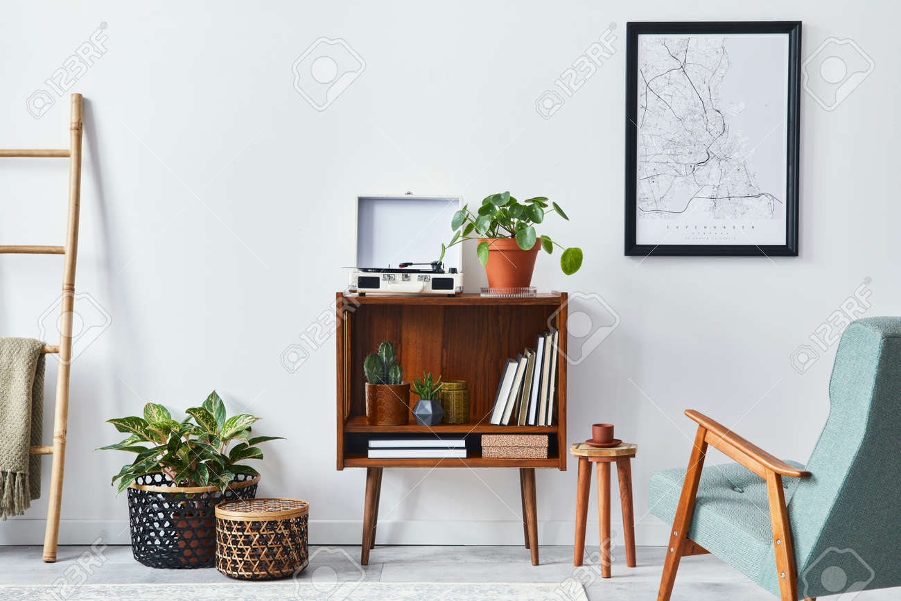 Modern retro composition of living room interior with design wooden cabinet, stylish armchair, mock up poster map, plants, vinyl recorder, books and personal accessories in home decor. Template. - 168356324