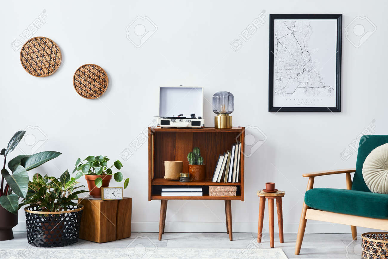 Stylish interior of living room with design wooden shelf, velvet sofa, a lot of plants, mock up poster map, vinyl recorder, book and personal accessories in vintage home decor. Template. - 168356328