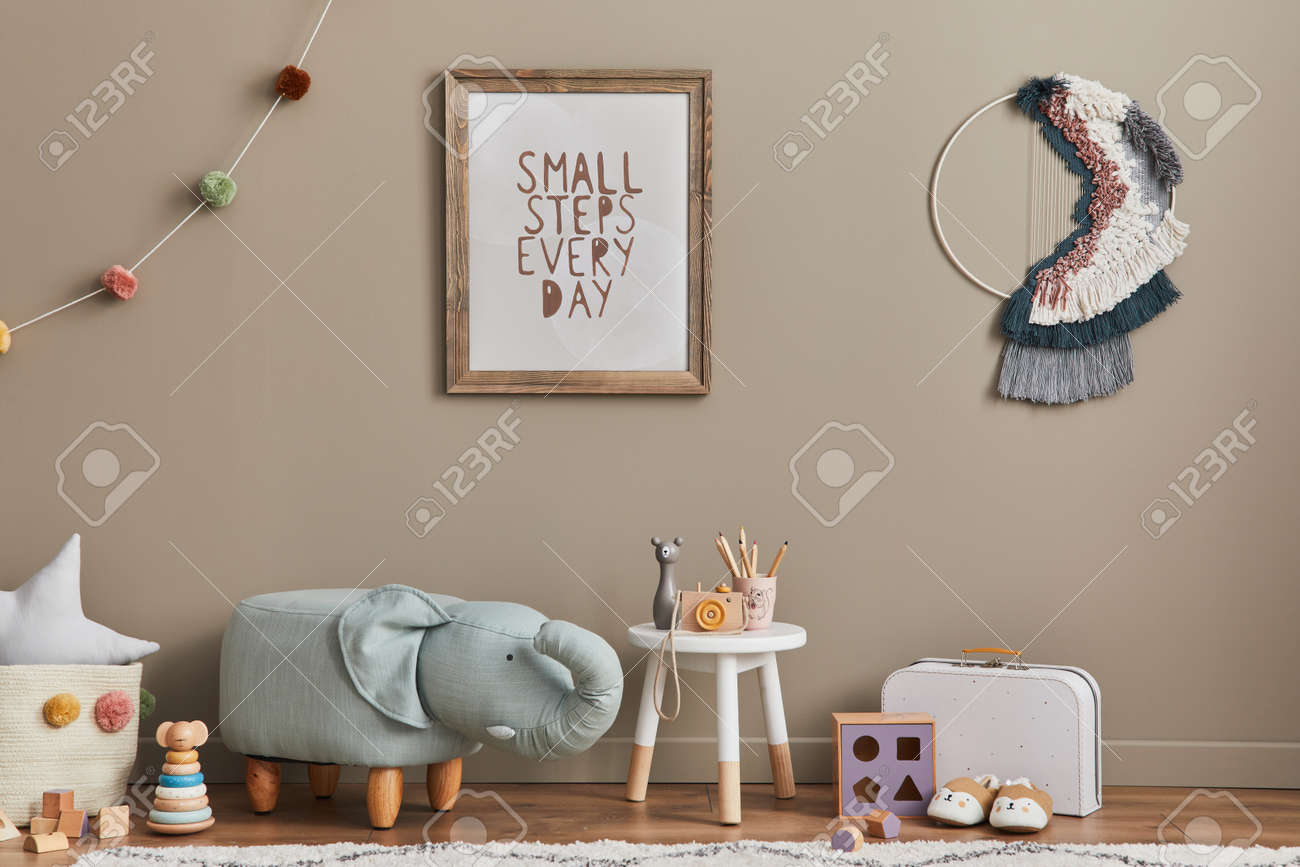 Stylish scandinavian kid room interior with toys, elephant pouf, plush animal toys, furniture, decoration and child accessories. Brown wooden mock up poster frames on the wall. Template - 168356332