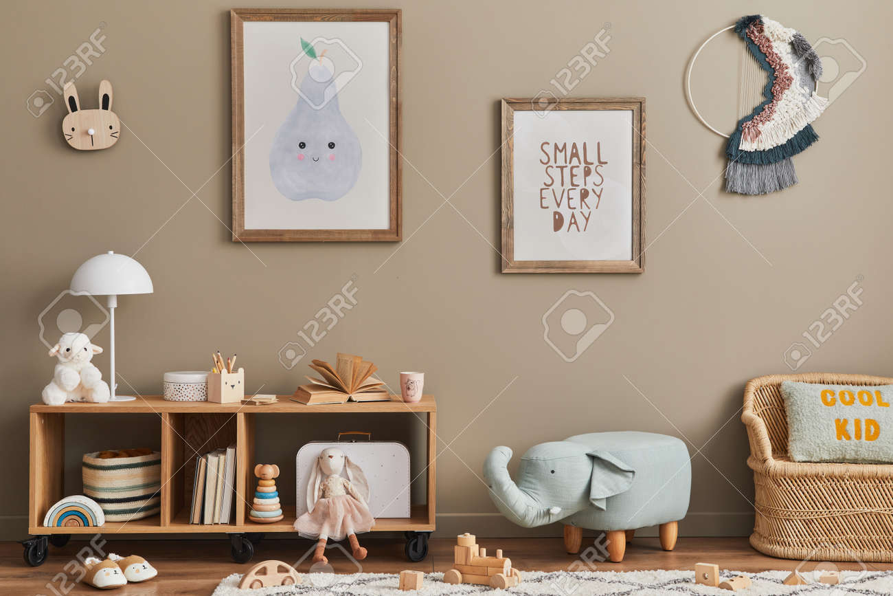 Stylish scandinavian kid room interior with toys, teddy bear, plush animal toys, mint armchair, furniture, decoration and child accessories. Brown wooden mock up poster frames on the wall. Template - 168356330