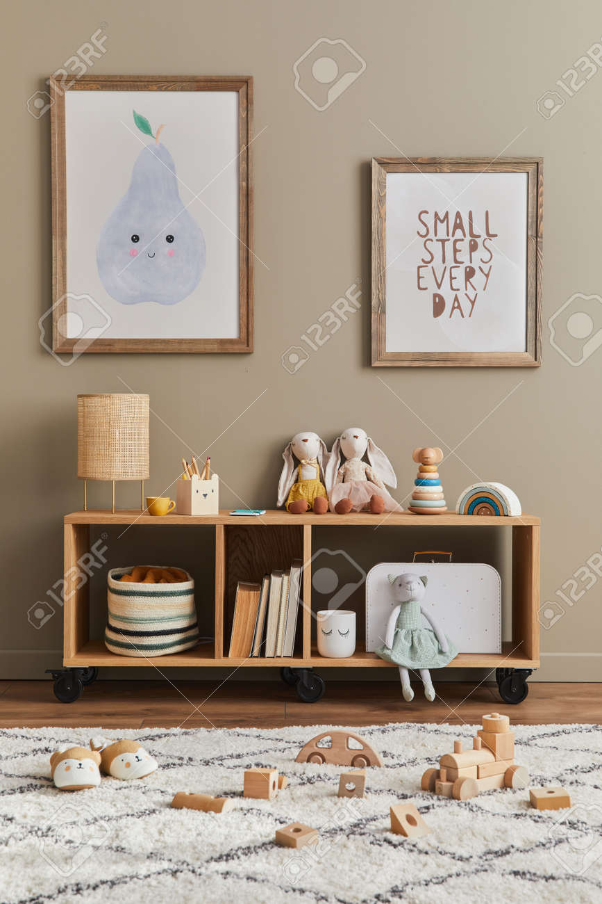 Stylish scandinavian kid room interior with toys, teddy bear, plush animal toys, furniture, decoration and child accessories. Brown wooden mock up poster frames on the wall. Template - 168356333