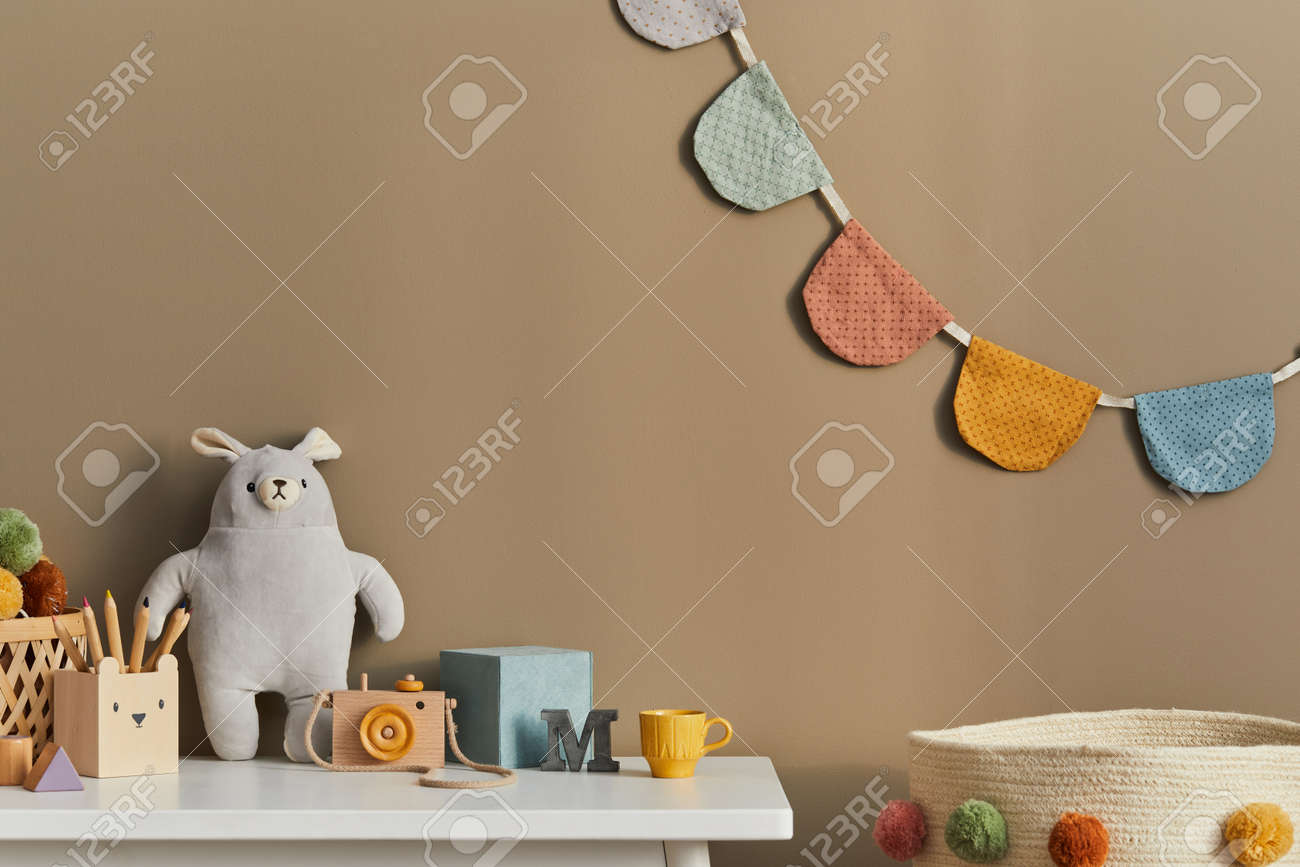 Interior design of stylish kid room space with white shelf, wooden toys, child accessories, cozy decoration and hanging cotton flags on the beige wall. Template. - 168356335