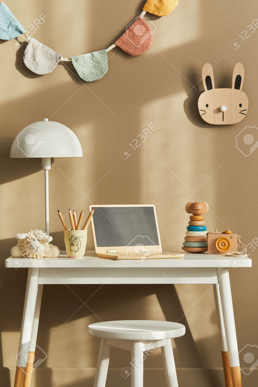 Interior design of stylish kid room space with white desk, wooden laptop, toys, child accessories, lamp, cozy decoration and hanging cotton flags on the beige wall. Template. - 168356383