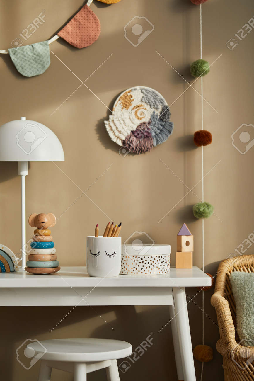 Interior design of stylish kid room space with white shelf, wooden toys, dolls, child accessories, white lamp, cozy decoration and hanging cotton flags on the beige wall. Template. - 168356378