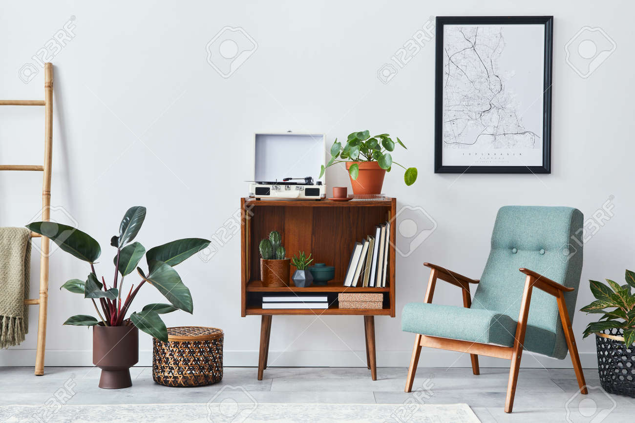 Modern retro composition of living room interior with design wooden cabinet, stylish armchair, mock up poster map, plants, vinyl recorder, books and personal accessories in home decor. Template. - 168356374