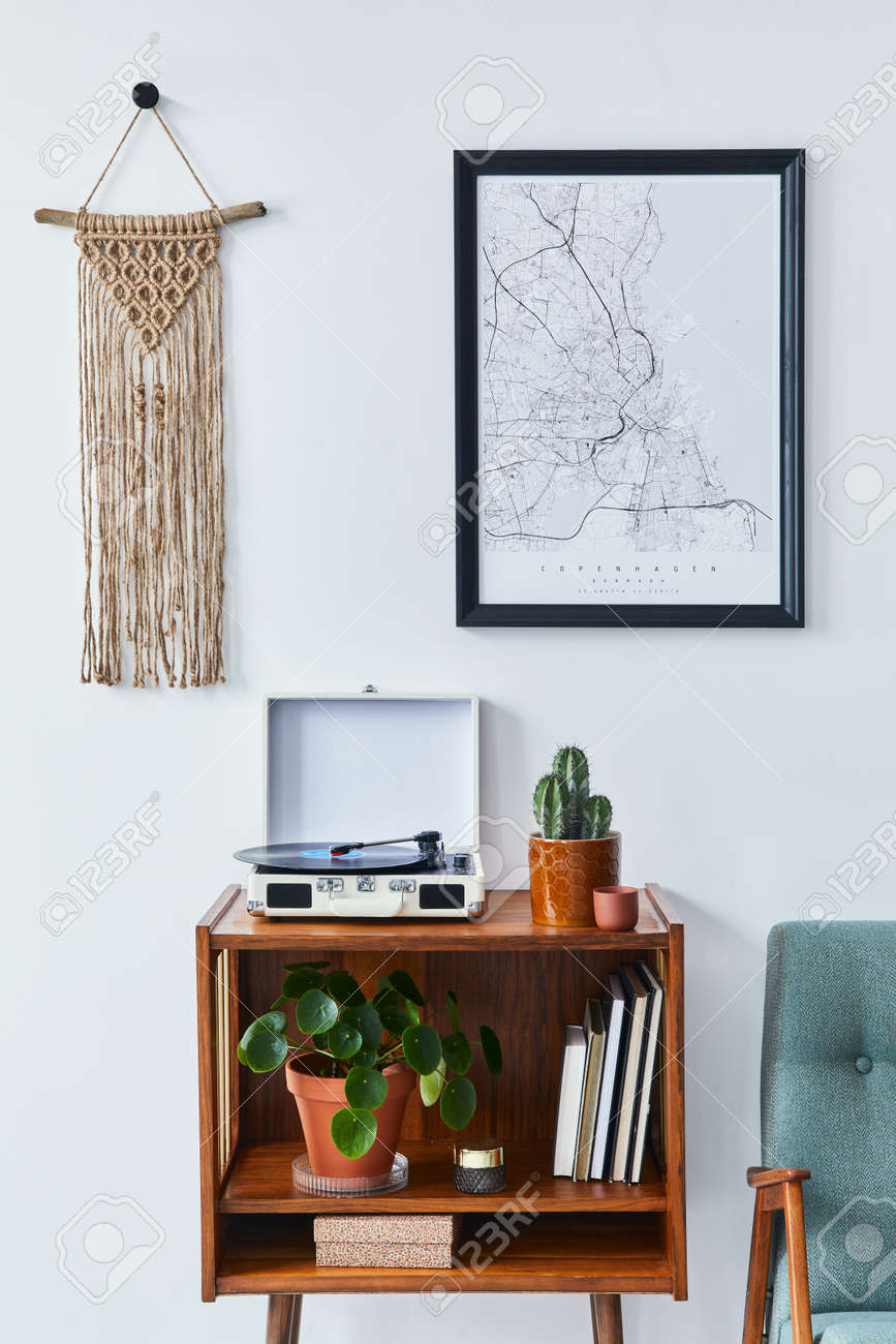 Retro composition of living room interior with mock up poster map, wooden shelf, book, macrame, armchair, plant, cacti, vinyl recorder and personal accessories in stylish home decor. - 168356390