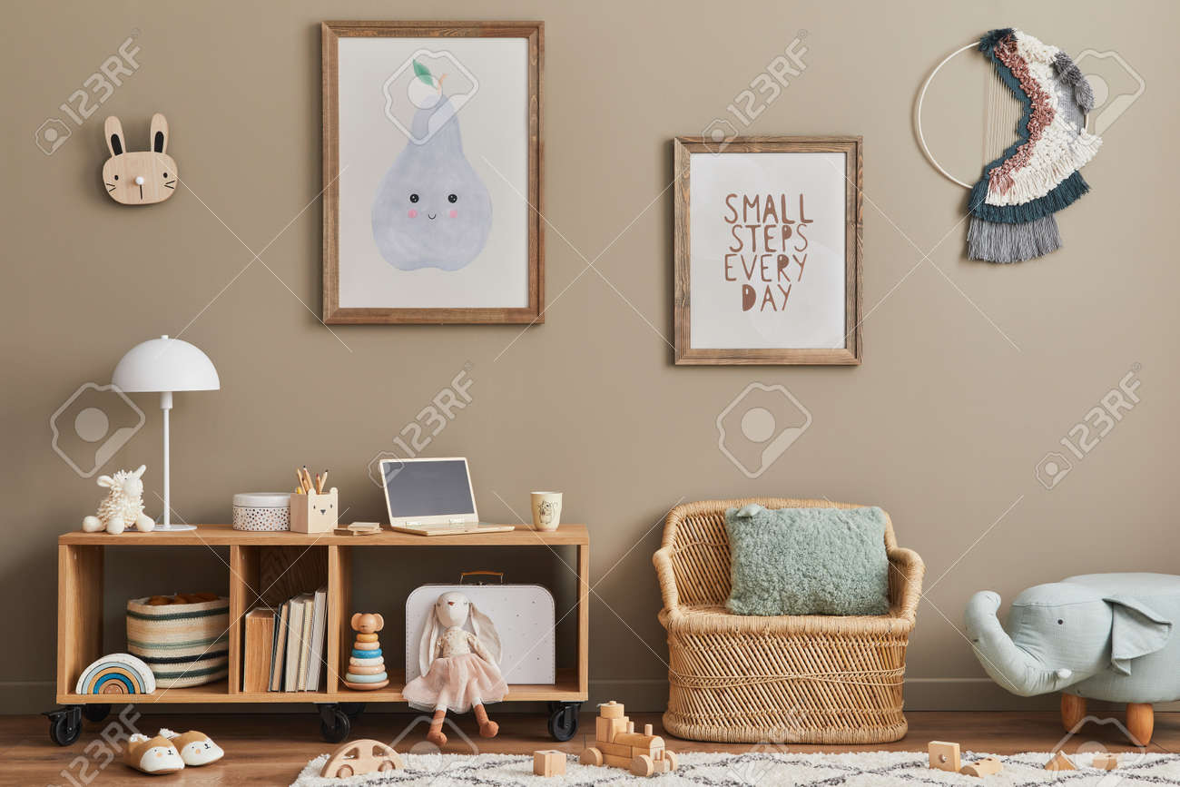 Cozy interior of child room with mint armchair, brown mock up poster frame, toys, teddy bear, plush animal, decoration and hanging cotton colorful balls. Beige wall. Warm kid space. Template. - 168356610