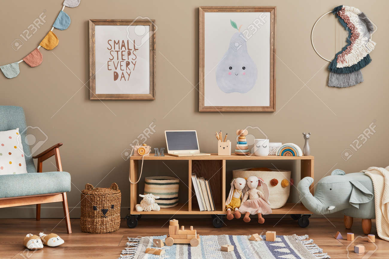 Stylish scandinavian kid room interior with toys, teddy bear, plush animal toys, mint armchair, furniture, decoration and child accessories. Brown wooden mock up poster frames on the wall. Template - 168356607