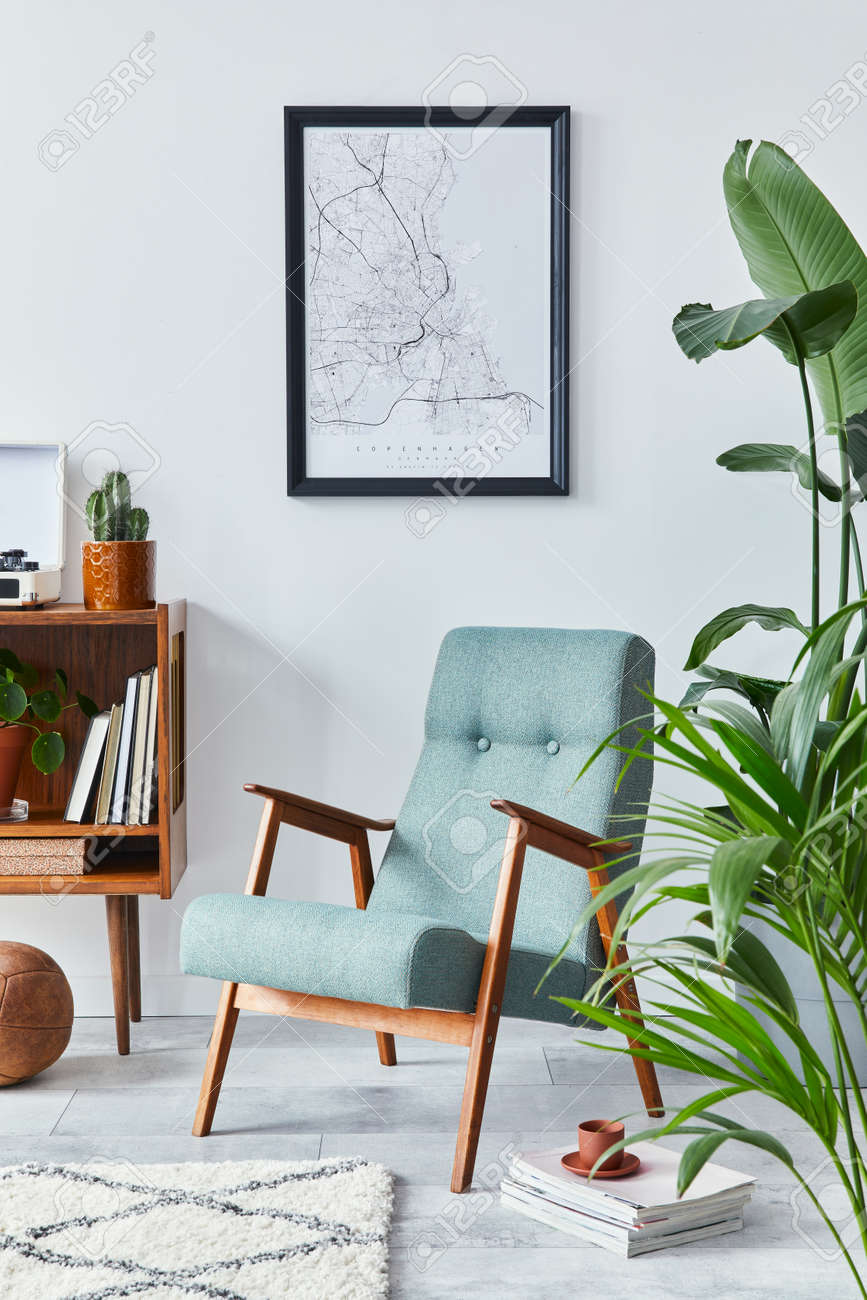Stylish interior of living room with design wooden shelf, retro armchair, plants, mock up poster map, decoration, book, cacti and personal accessories in retro home decor. Template. - 168356618