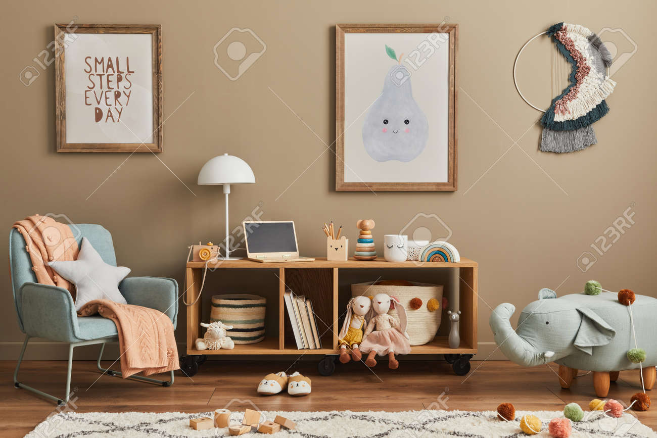 Stylish scandinavian kid room interior with toys, teddy bear, plush animal toys, mint armchair, furniture, decoration and child accessories. Brown wooden mock up poster frames on the wall. Template - 168356616