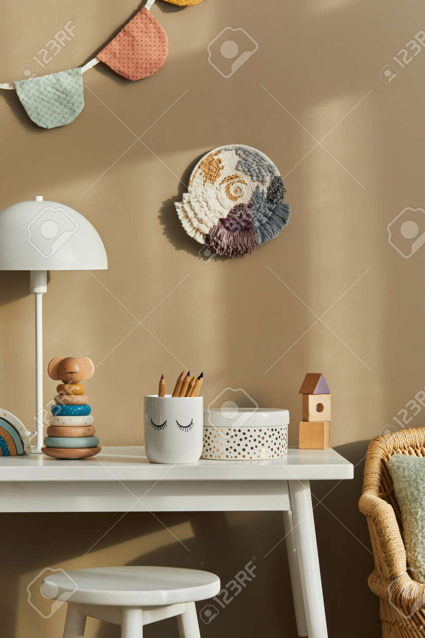 Interior design of stylish kid room space with white desk, wooden toys, child accessories, white lamp, cozy decoration and hanging cotton flags on the beige wall. Template. - 168356726