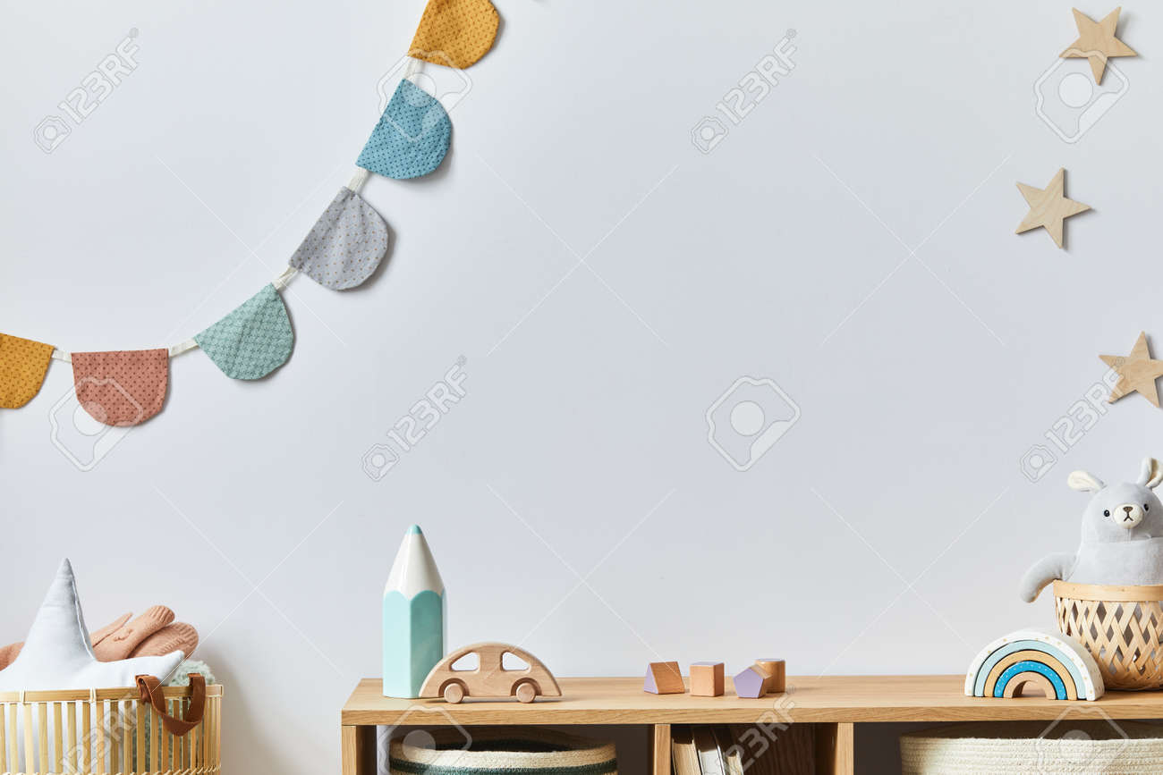 Stylish scandinavian newborn baby room with toys, plush animal, photo camera and child accessories. Cozy decoration and hanging cotton balls on the white wall. Copy space. - 168356732