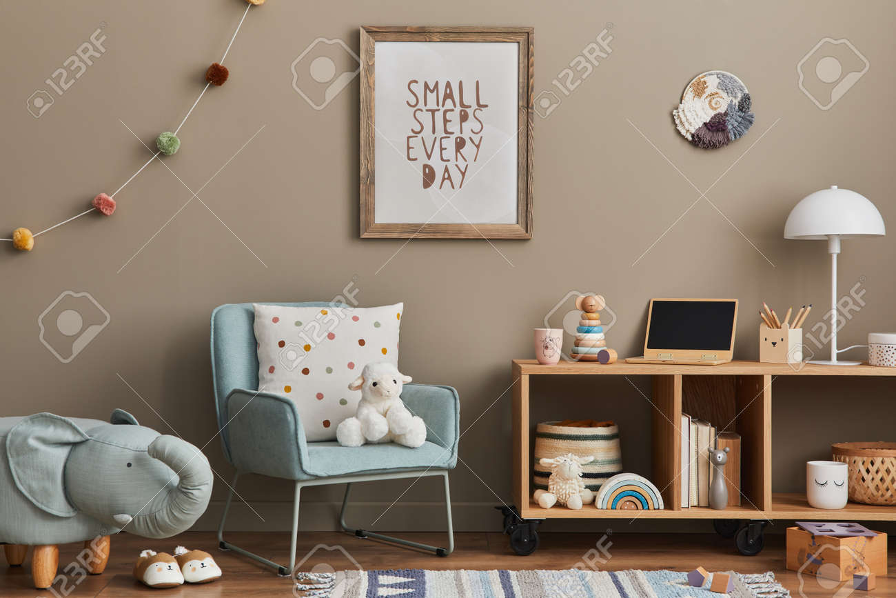 Cozy interior of child room with mint armchair, brown mock up poster frame, toys, teddy bear, plush animal, decoration and hanging cotton colorful balls. Beige wall. Warm kid space. Template. - 168356736