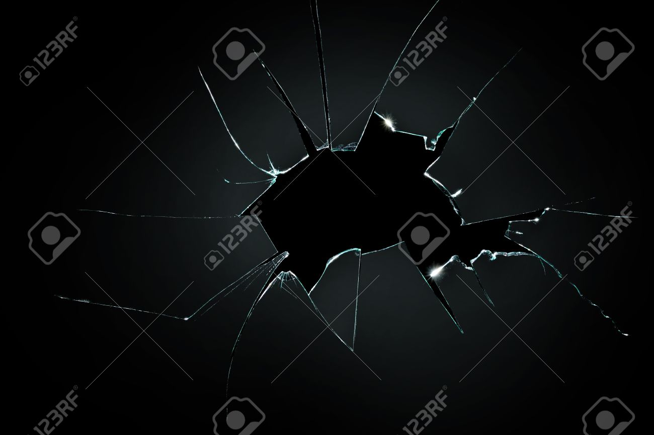broken cracked glass with big hole over black background - 50929548
