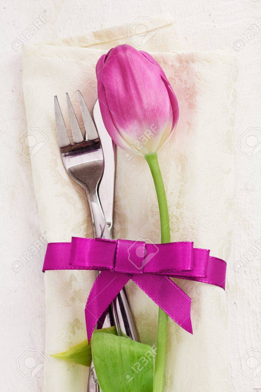 Napkin with tulip Flower. Dinner Table setting for two with a pink ribbon and a fork and a knife on wooden white background Stock Photo - 12640218