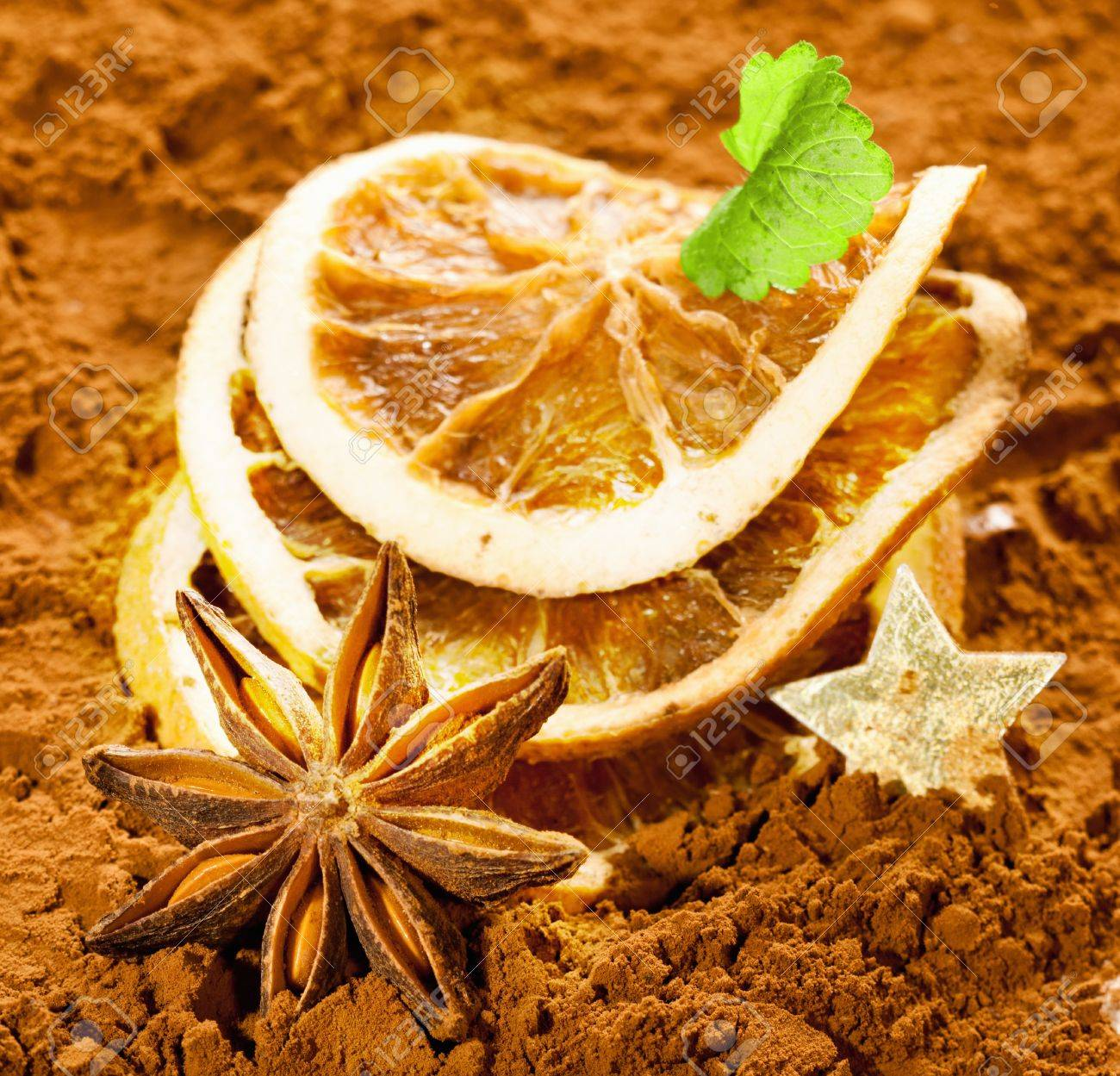 Dried orange slices with anise and a golden star on a brown background Stock Photo - 12640219
