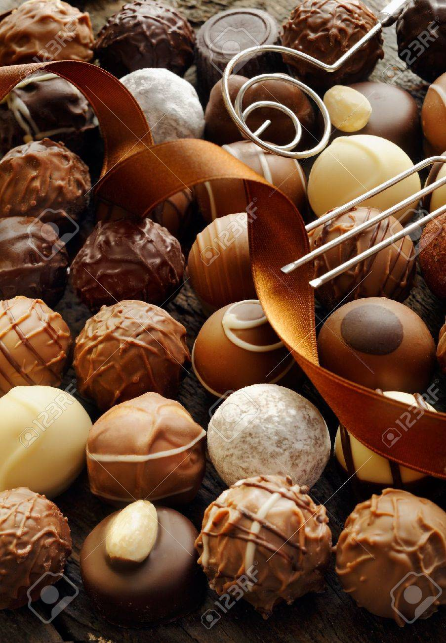 Background of an assortment of different decorative luxury chocolates with an ornamental ribbon Stock Photo - 12926808