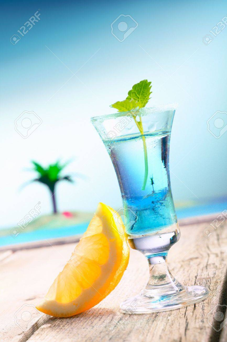 Blue Curacao Beach Cocktail with fresh lemon standing on a landing stage, with the pacific and a lagoon with a palm in the background. More Drinks in my portofolio. - 13179780