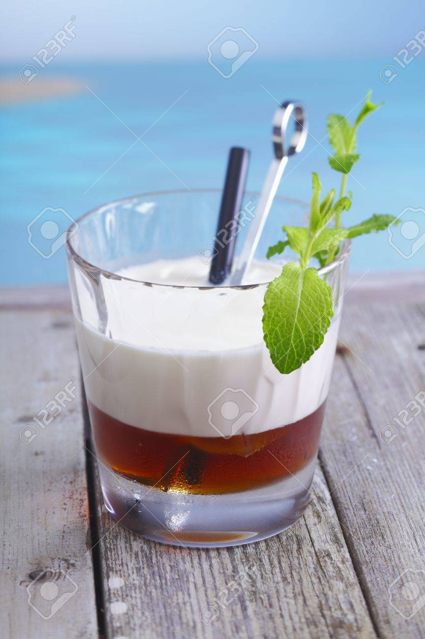 White Russian Coffee Cocktail with ice cubes and cream topping standing in a lounge at the beach, for alcoholic Drink Concepts. Visit my portfolio for more inspirations. Stock Photo - 13179779