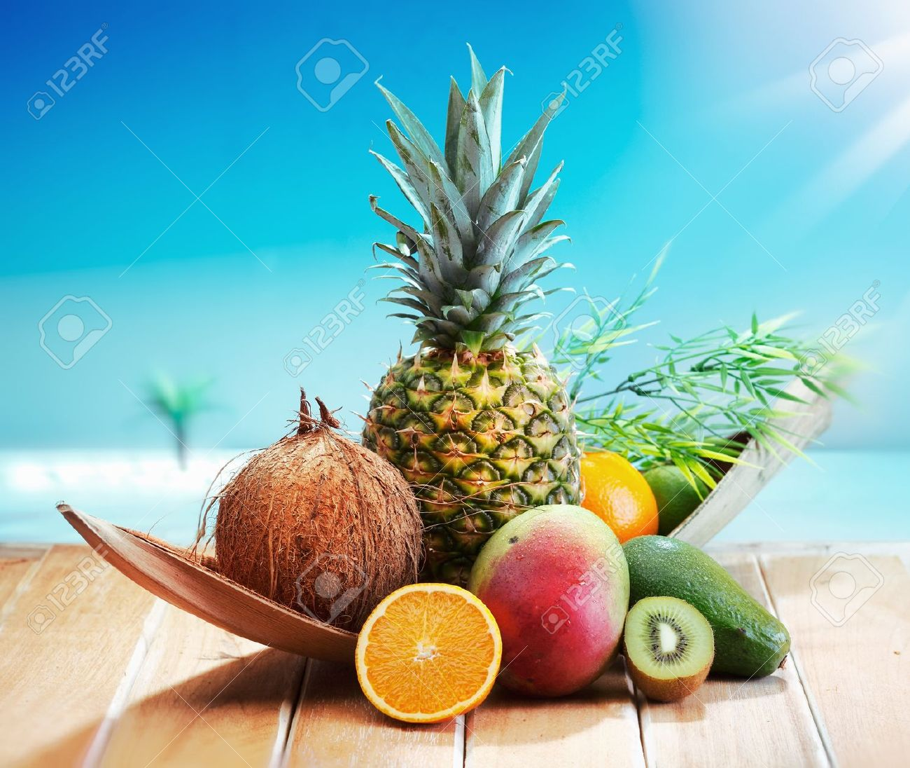 Fresh Fruits on the beach at a deck in front of an island with a palm. Assorted tropical fruits, orange,Ananas or pineapple, lime,mango and avocado. - 13237748