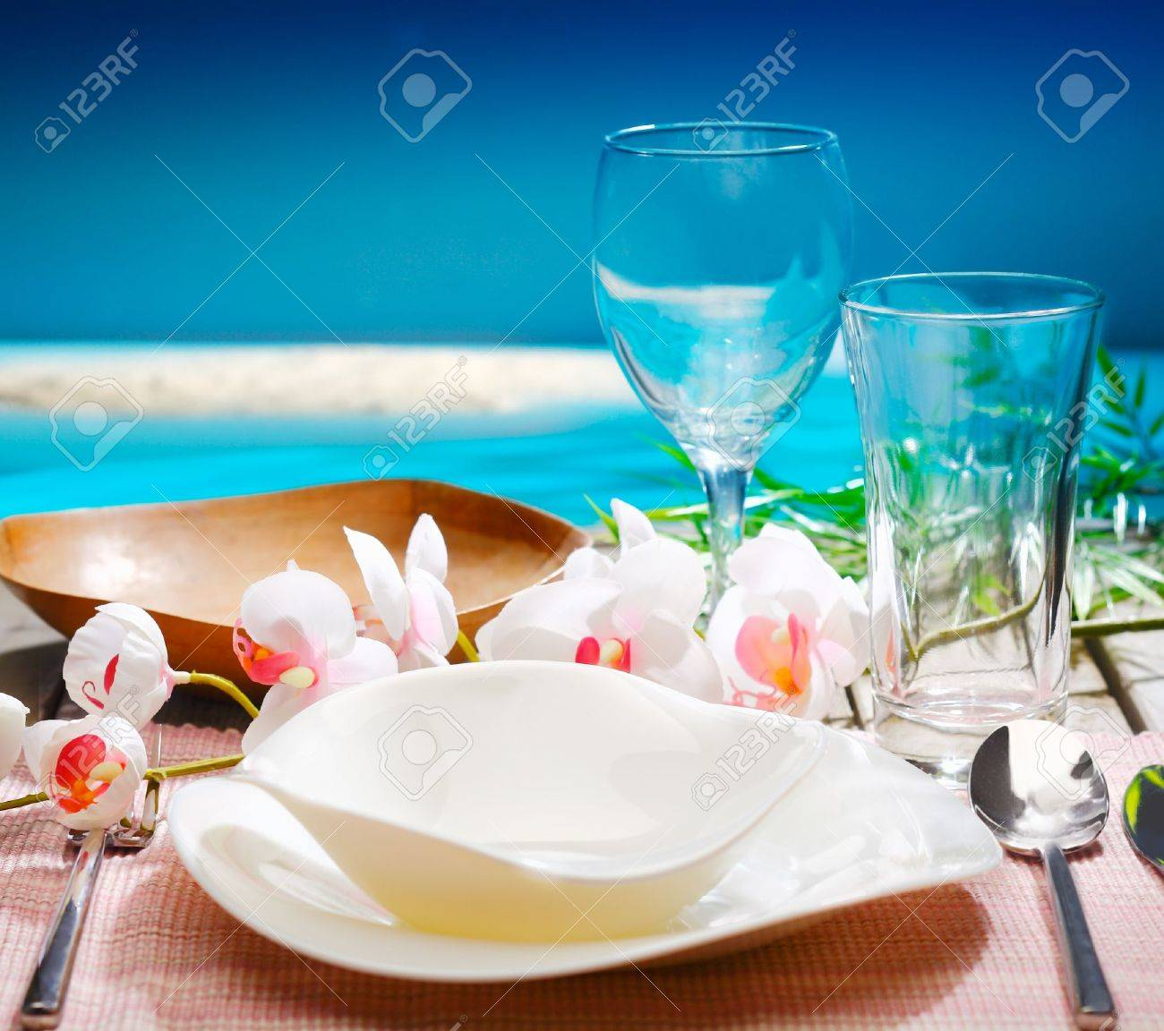 Restaurant table setting for two - Table For Two Decorative Tropical Table Setting With Stylish Dinnerware And Orchids Overlooking The Ocean