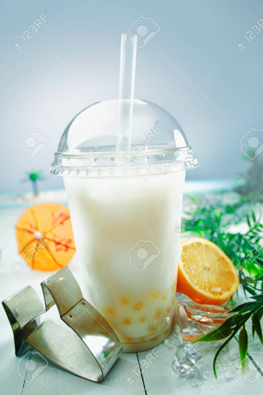 Milky bubble tea blended with fresh orange fruit and boba or tapioca balls served at the sea Stock Photo - 13567045