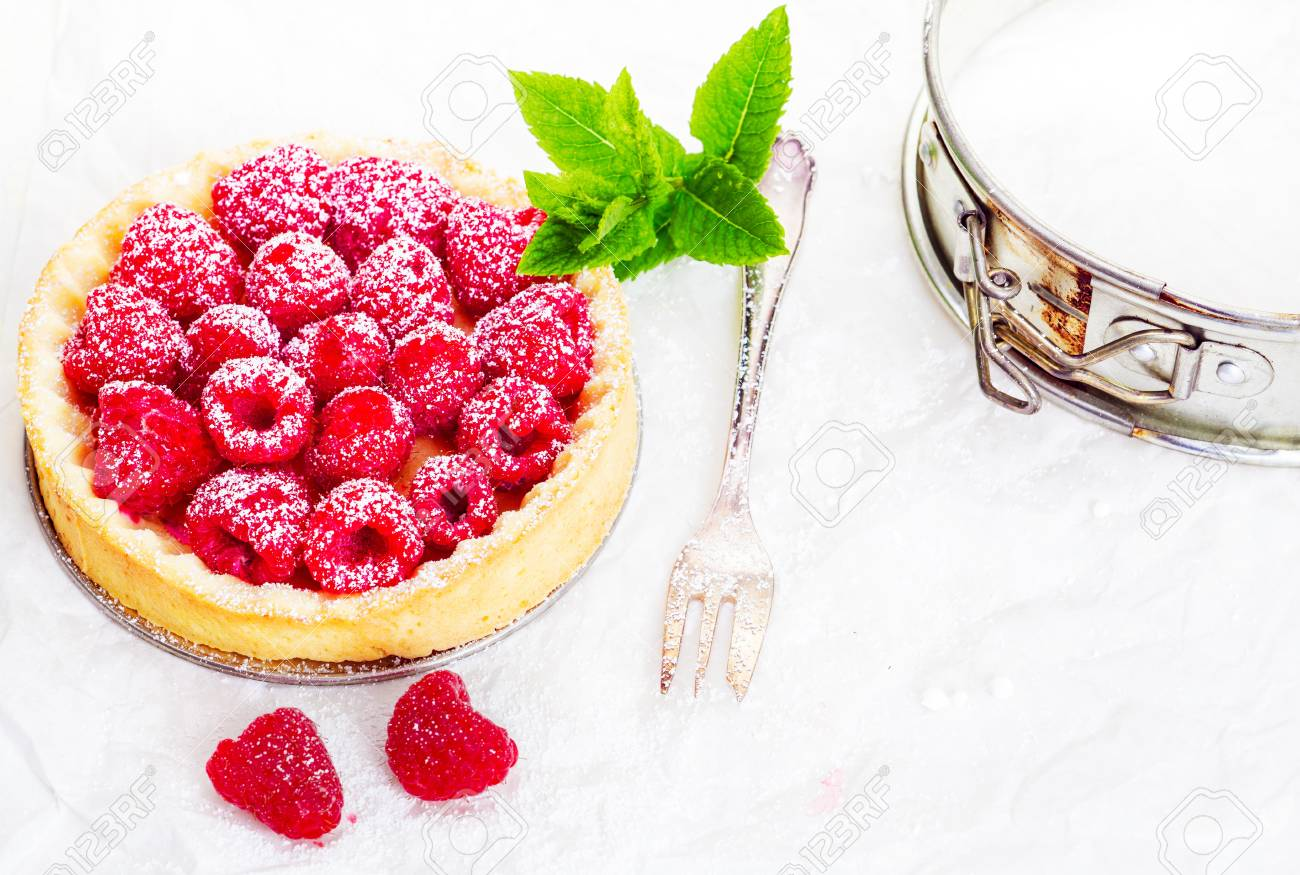 High angle view of a delicious freshly baked raspberry pie in a golden pie crust garnished with a sprig of mint and served with a silver fork Stock Photo - 14320616