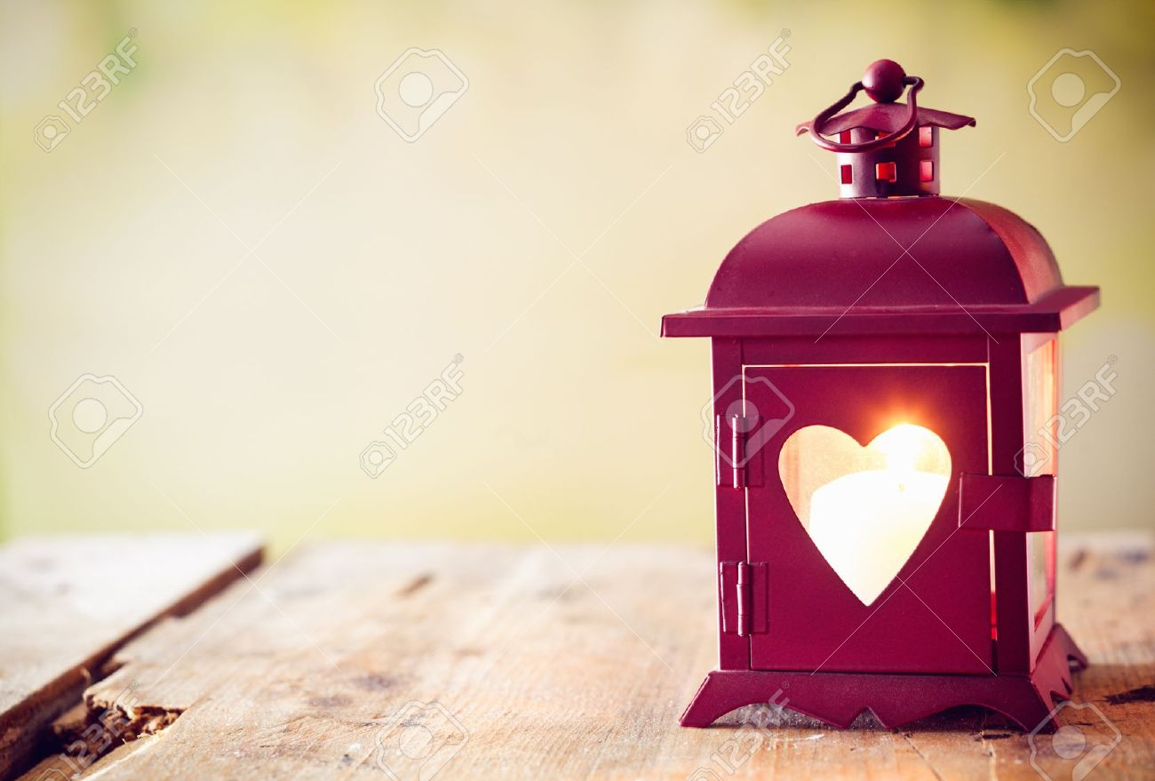 Decorative red metal lantern with a heart cutout lit by a glowing candle with copyspace for Valentines or Christmas Stock Photo - 14759892
