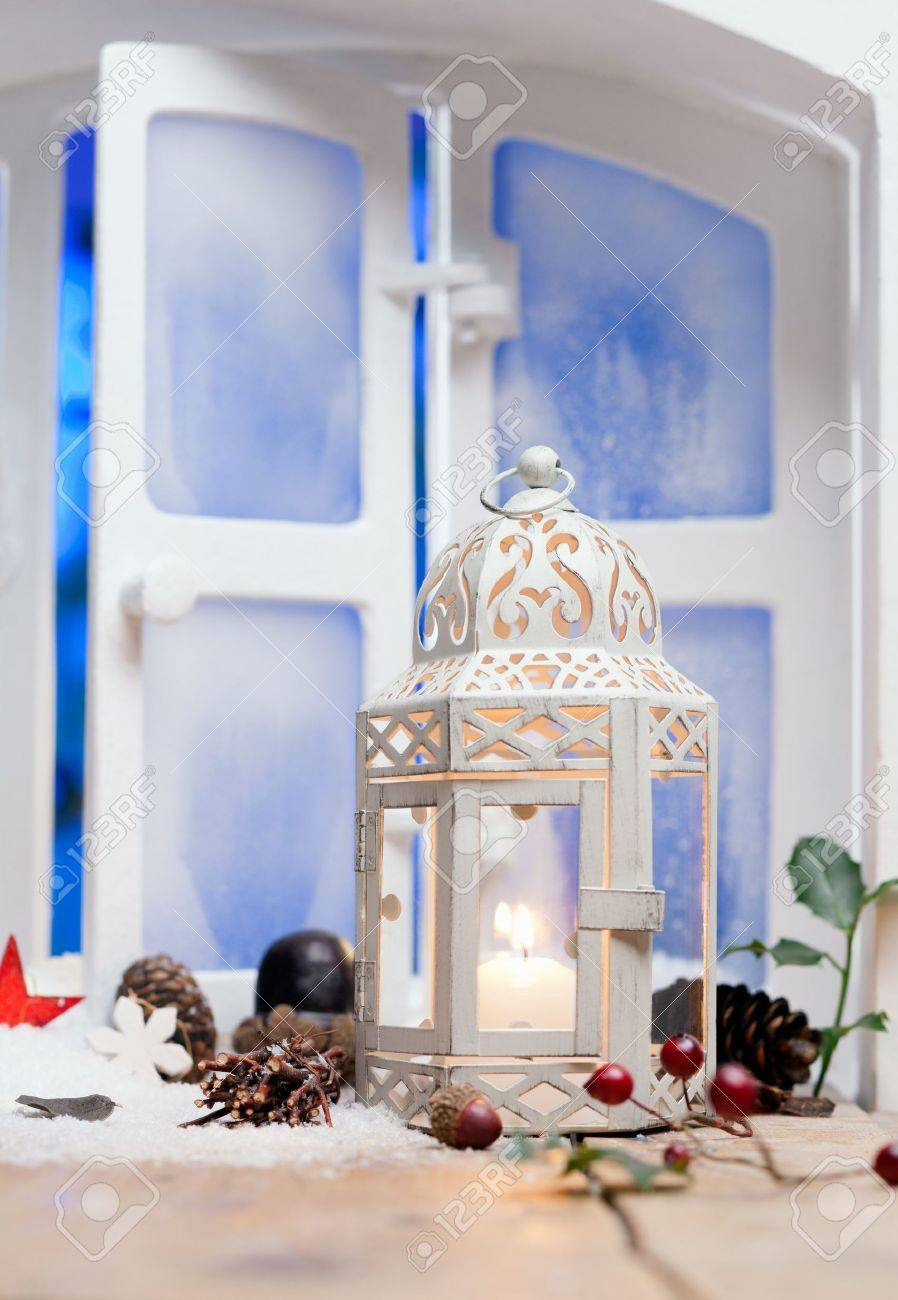 Pretty white Christmas lantern with a burning candle on a windowsill surrounded by decorative cones and berries Stock Photo - 15213910