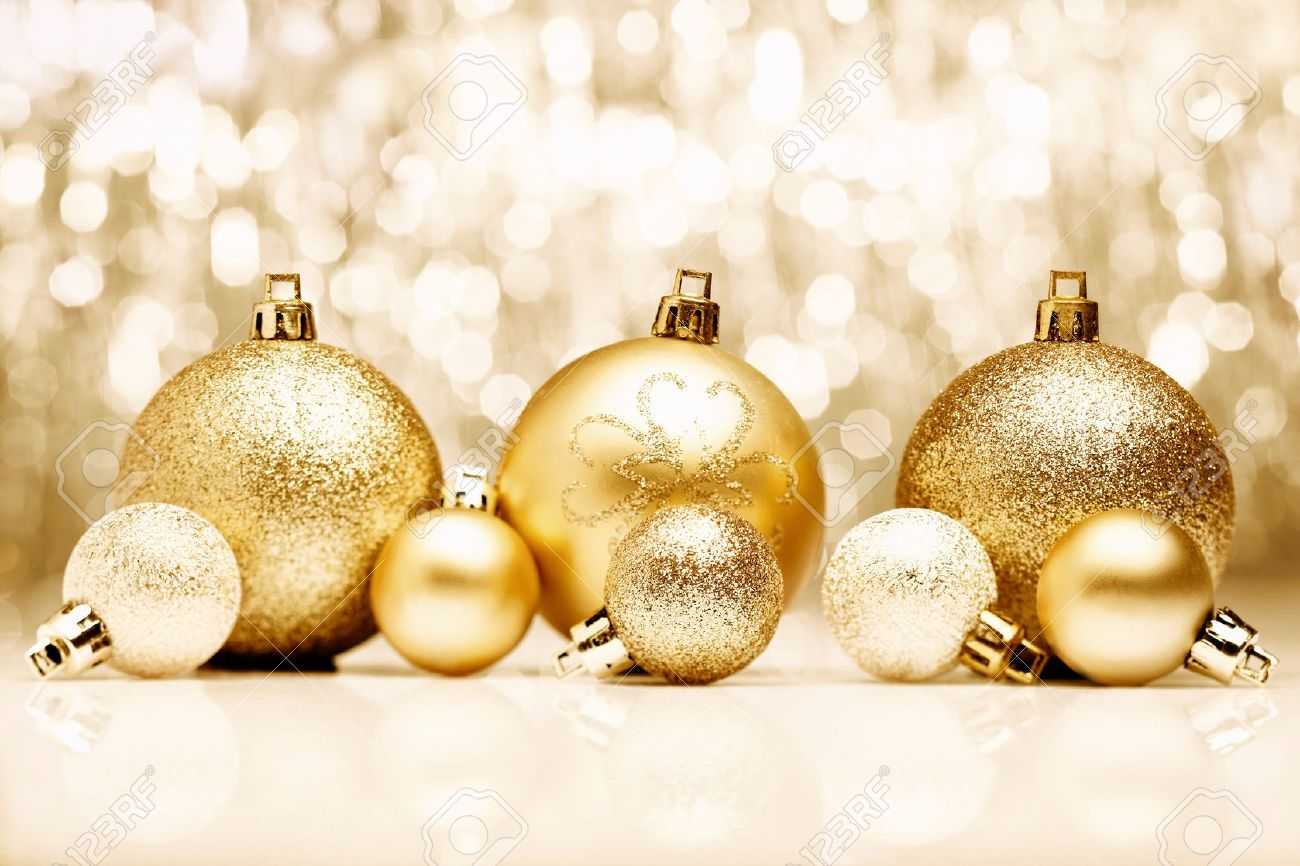 An arrangement of golden Christmas baubles against a festive bokeh of twinkling gold lights with copyspace Stock Photo - 15213904