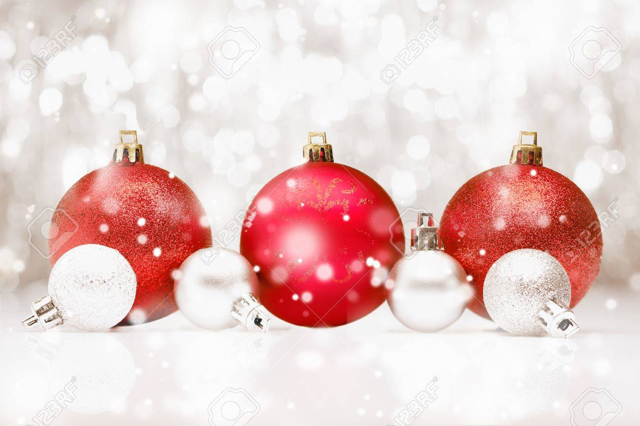 Background of red Christmas baubles in falling snow with bokeh and copyspace for your seasonal greetings Stock Photo - 15213889