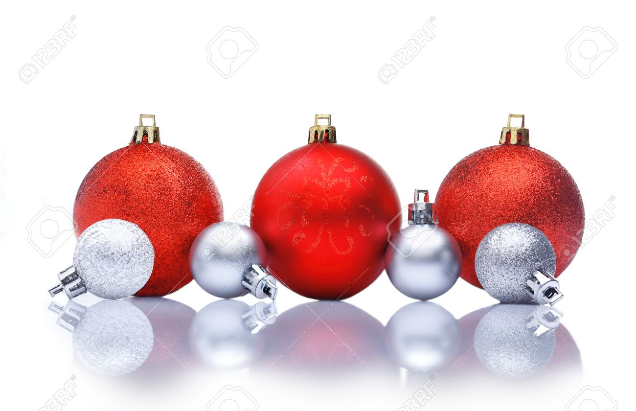 Red and silver Christmas decorations in a row with reflections and  copyspace for your Christmas greetings
