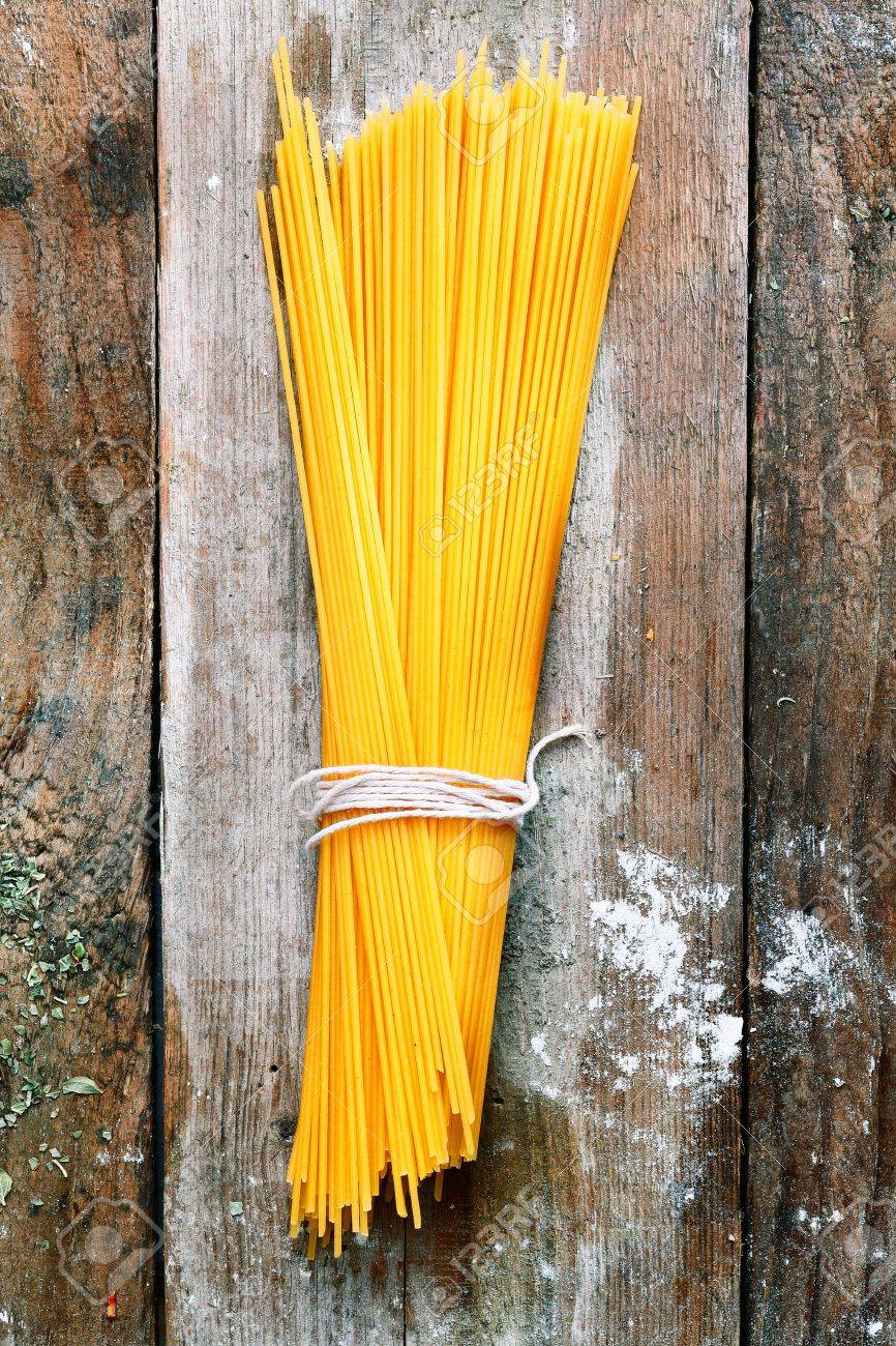 Bundle of Italian spahgetti pasta tied with string lying on old textured wooden boards with a scattering of flour Stock Photo - 15179079