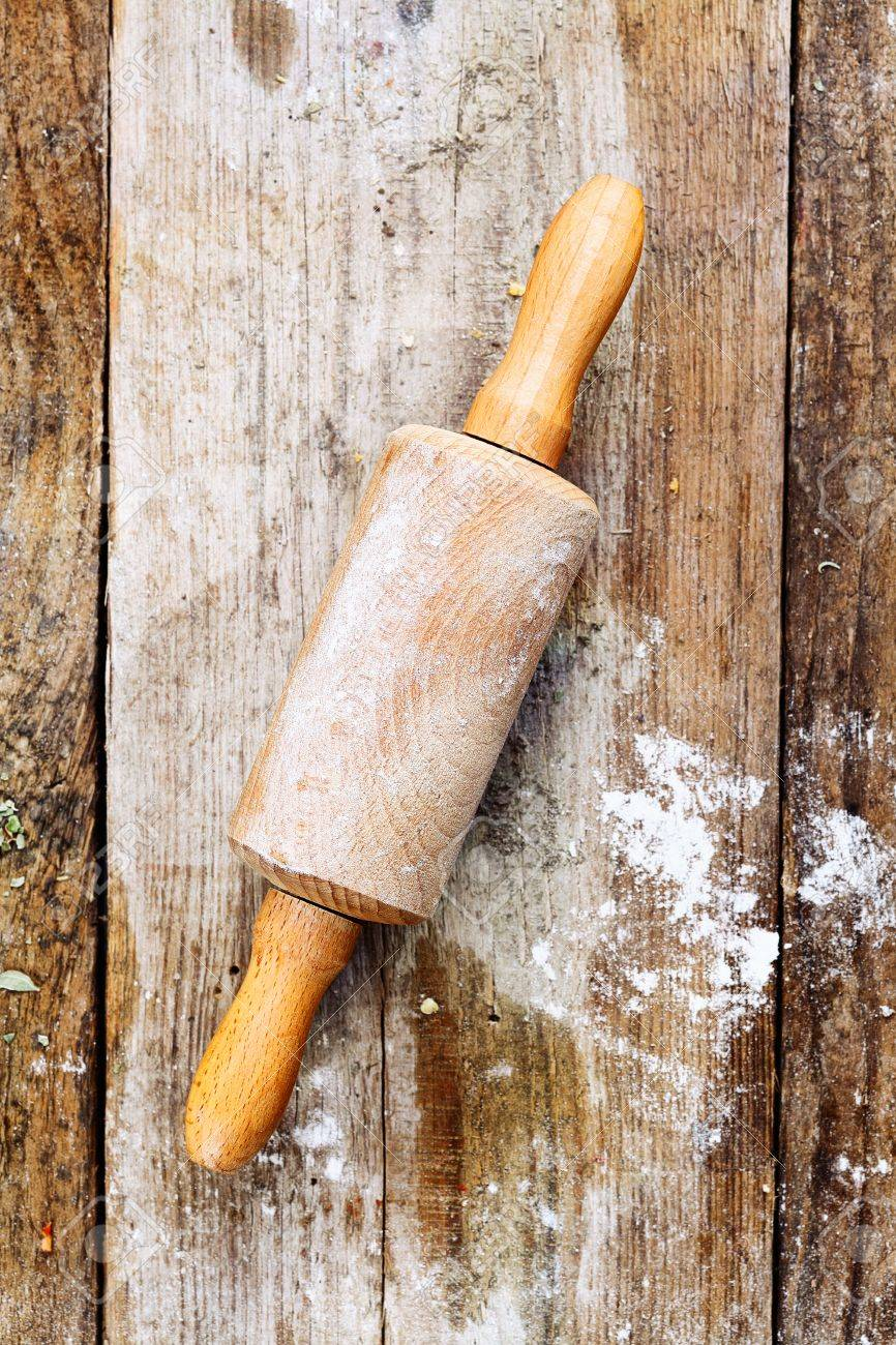 Wooden rolling pin with remnants of flour in a rustic kitchen on an old grainy textured wood surface Stock Photo - 15179076