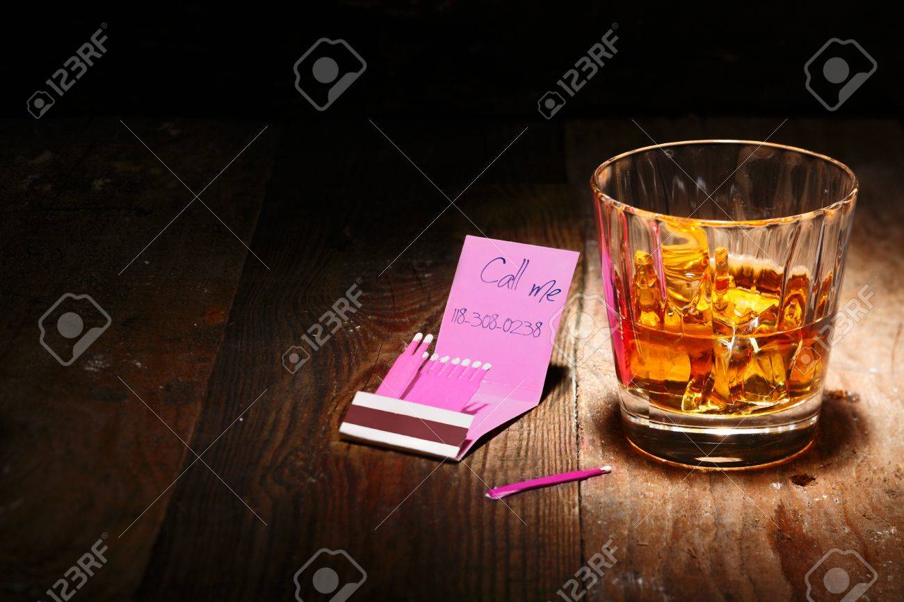Whiskey on the Rocks or Scotch with a book of matches with a phone number insight Stock Photo - 15179082