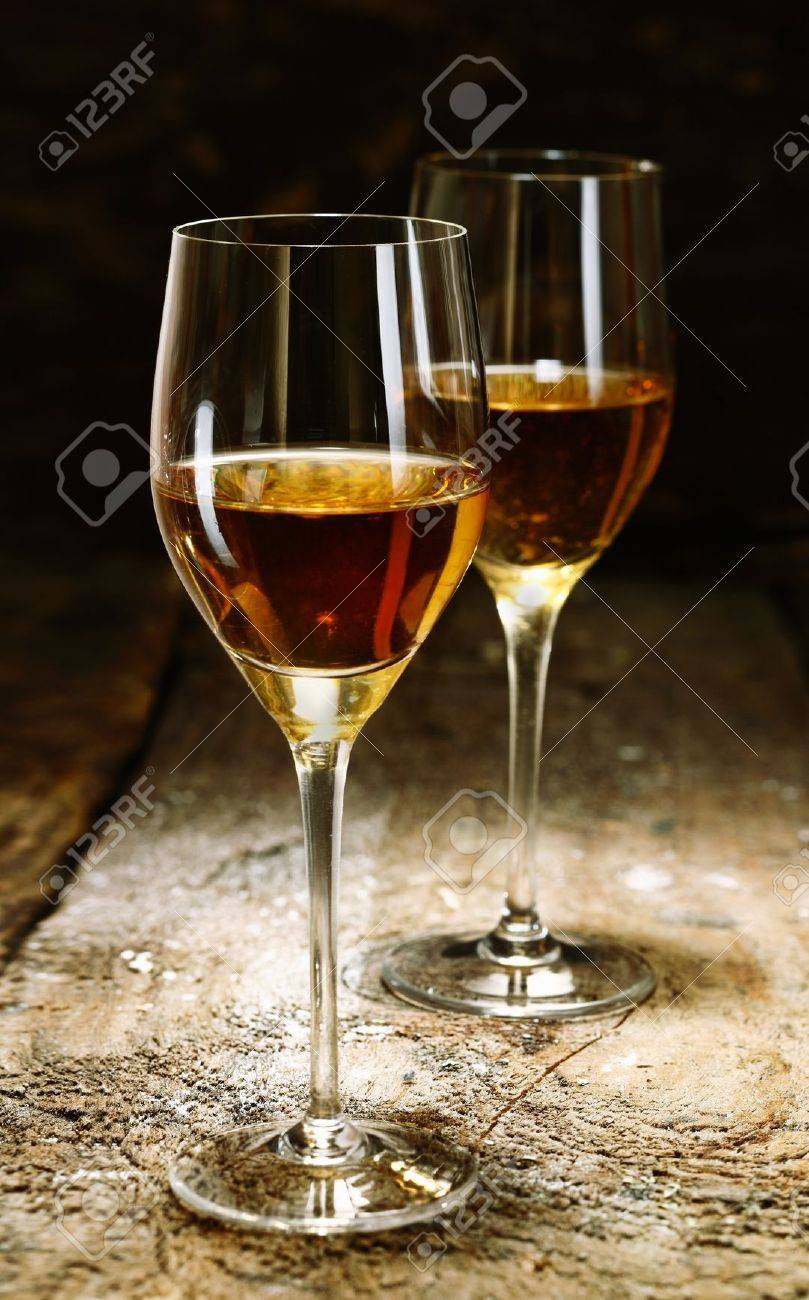 Two glasses of sherry on brown wooden background Stock Photo - 15503885