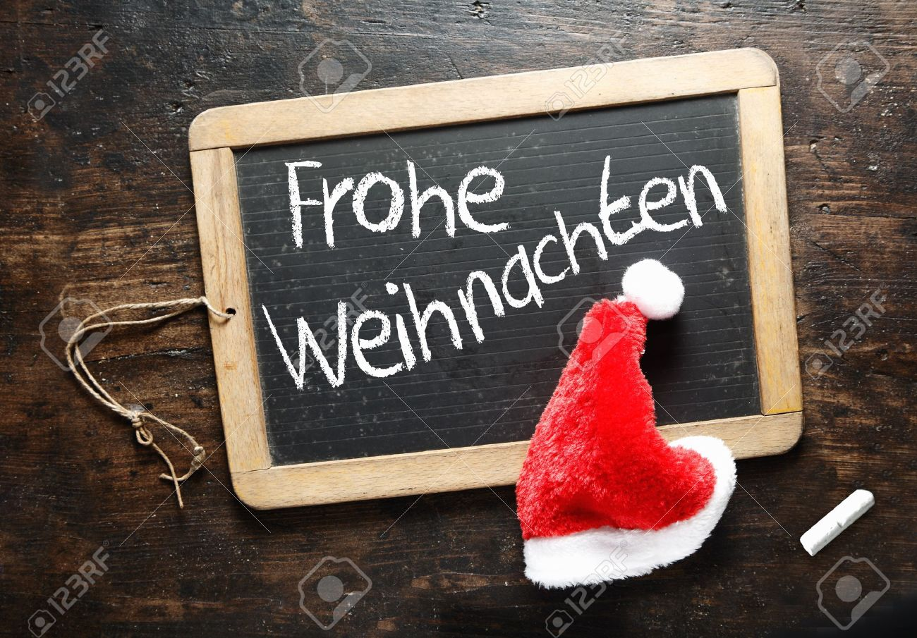 Frohe Weihnachten Christmas greeting handwritten in German on a chalkboard slate with a colourful red Santa hat Stock Photo - 15847528
