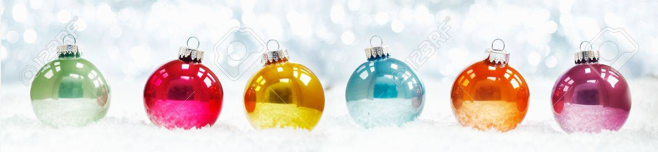 Beautiful shiny Christmas ball banner arranged in a row on fresh white winter snow with a backdrop of sparkling lights Stock Photo - 15847551