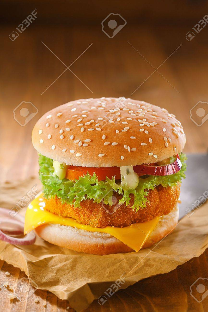 Delicious chicken burger with a golden crumbed patty and salad ingredients on grungy crumpled brown paper against a wooden backdrop with copyspace - 17853205
