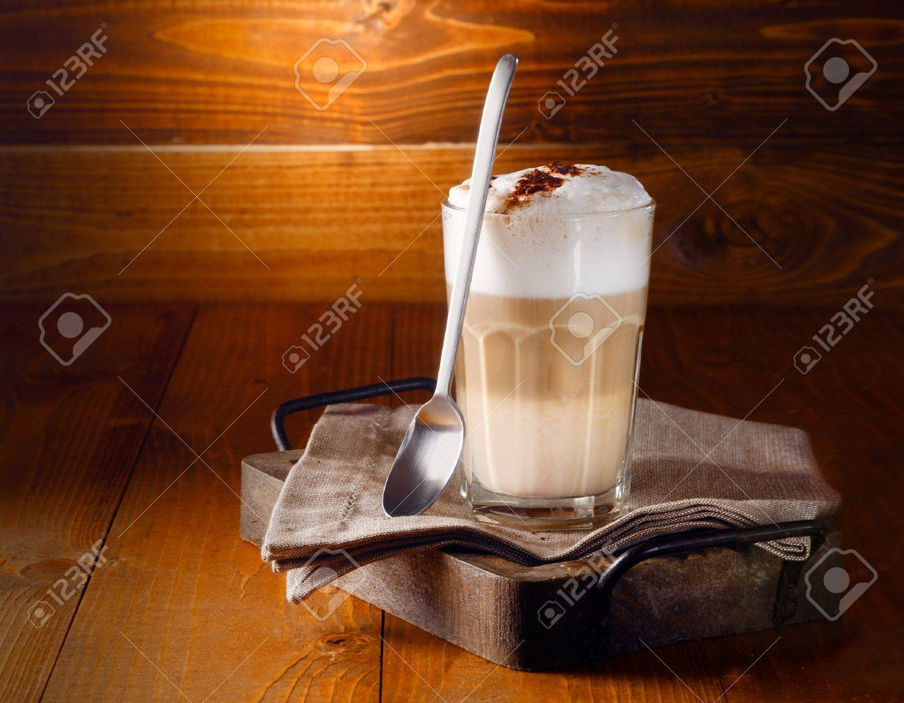 Delicious layered cappuccino or latte macchiato coffee served in a long glass with a spoon against a rustic wooden background with copyspace Stock Photo - 17853271