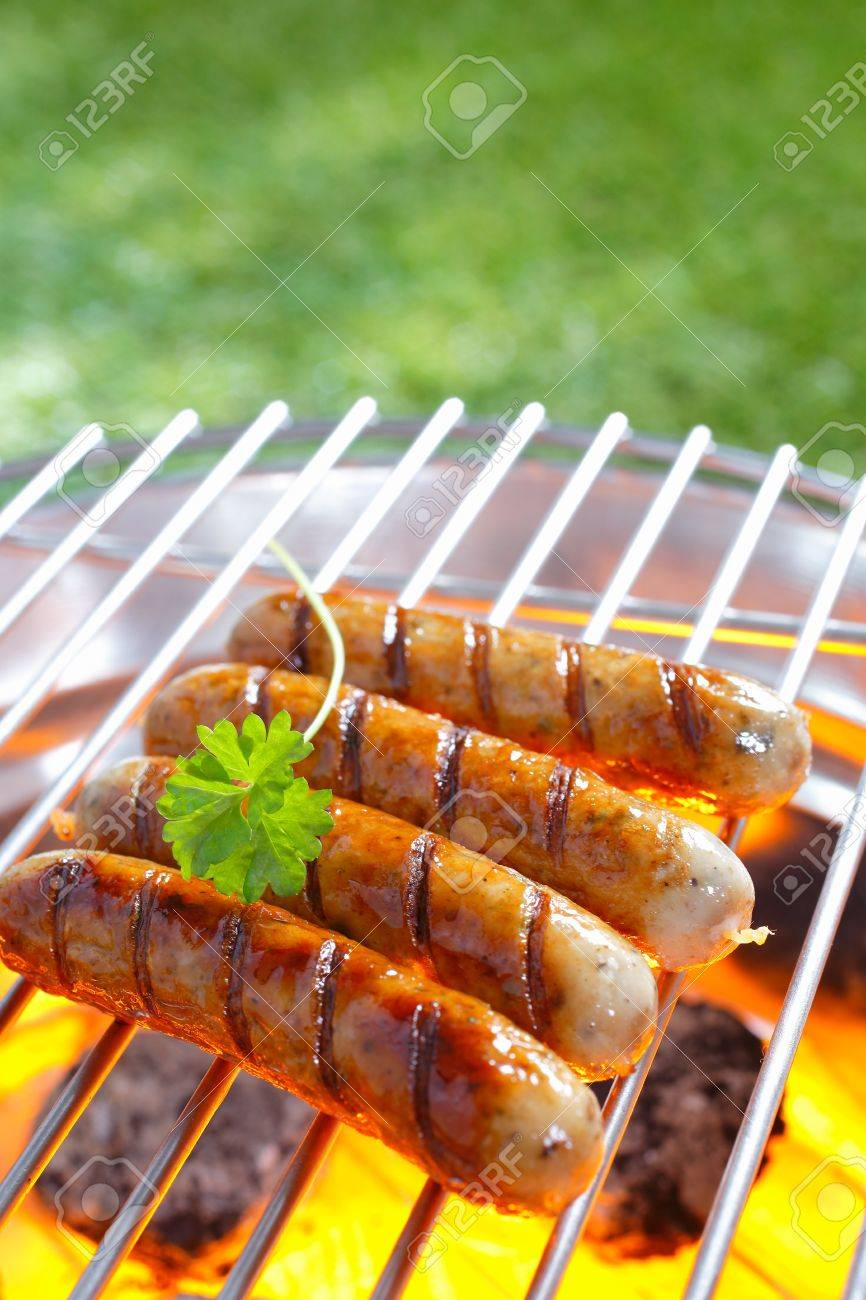Delicious grilled sausages resting on the iron grid of a portable barbecue over glowing coals as they cook to perfection - 18566083